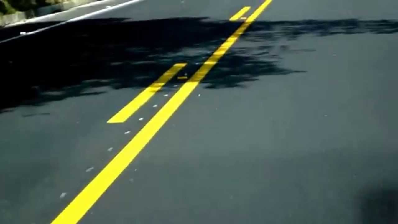 Linea amarilla discontinua sobre la que está prohibido estacionar y es pista solo buses