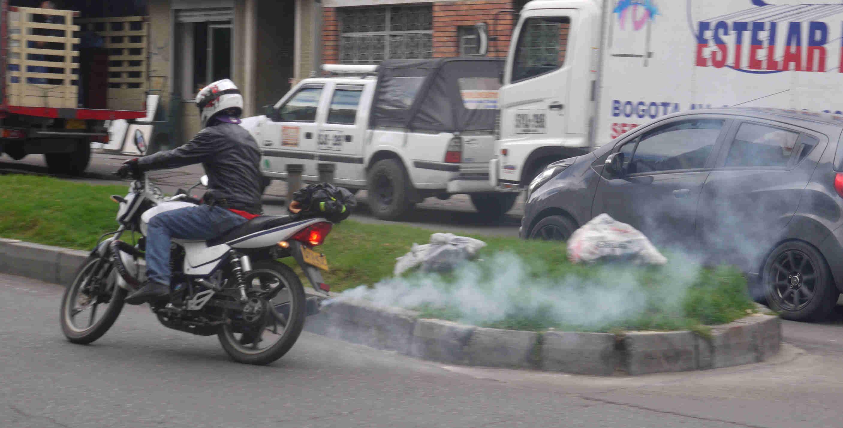 Motociclista emitiendo humo azul para contaminar el medio ambiente